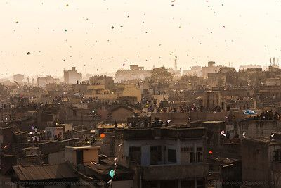 People gathered on terraces or rooftops of their houses everyone flying kites and the sky covered with tiny colourful dots of kites for the festival of Makar Sankranti or Uttarayan in the old Khadia area of Ahmedabad in Gujarat, India.