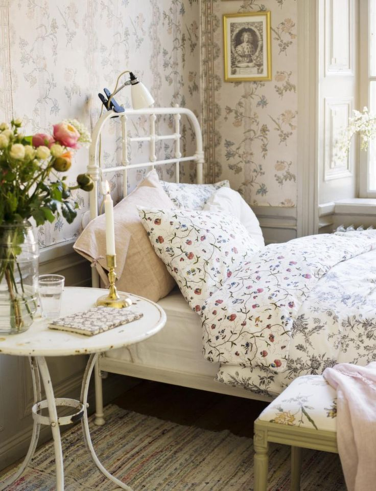 sweet little guest bedroom space - painted metal bed and table, white lamp, pale linens and wallpaper