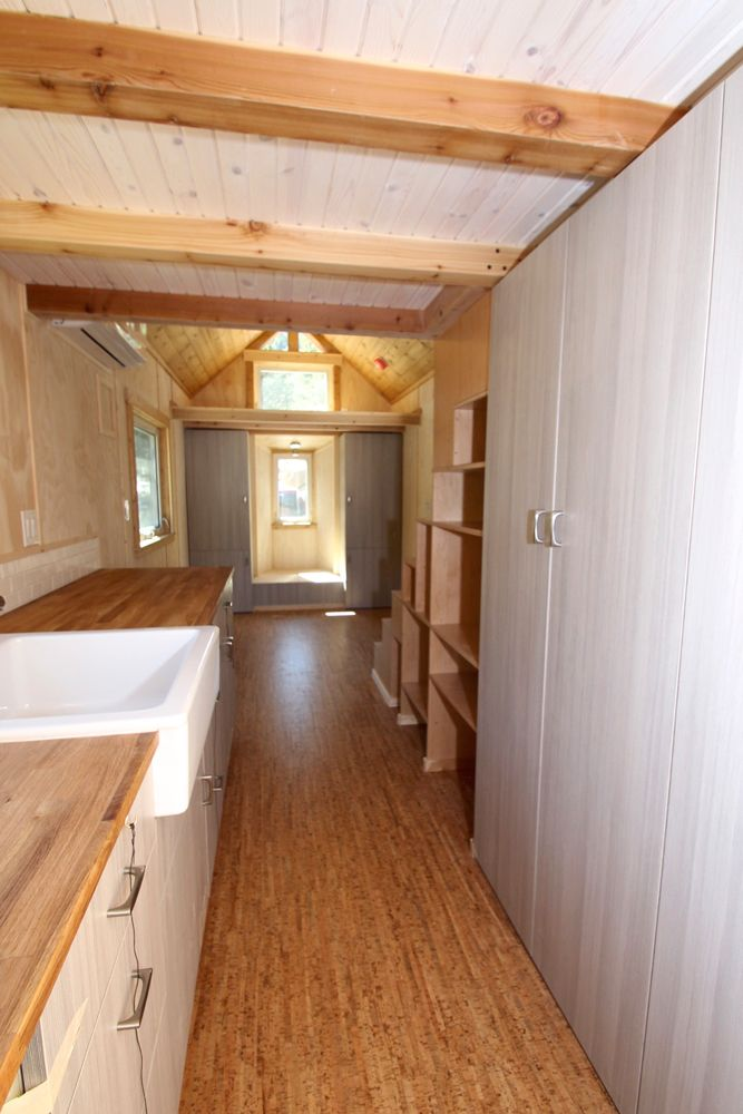 The kitchen has a four burner gas stove, apartment size refrigerator, and large pantry.
