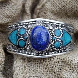Lapis lazuli armband  Armband versierd met een Lapis Lazuli steen.   Handgemaakt van Tibetaans zilver door ambachtslieden in Nepal, volgens traditionele Tibetaanse techniek. Breedte: 4 cm.   Instelbaar door de open achterkant.