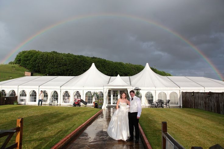 wedding marquee with a rainbow in the background.