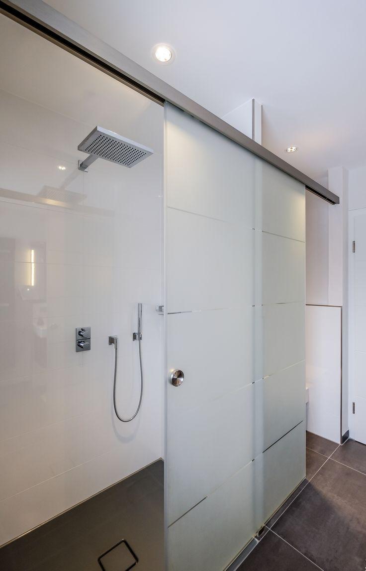Die bodengleiche Dusche befindet sich hinter einer Schiebetür