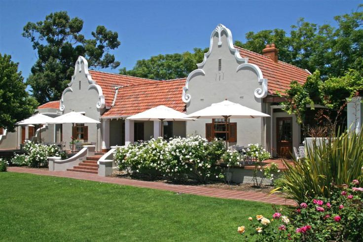 Cape Dutch style house, set a midst rolling lawns and masses of ...