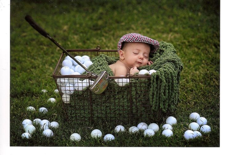 baby in crate with golf balls