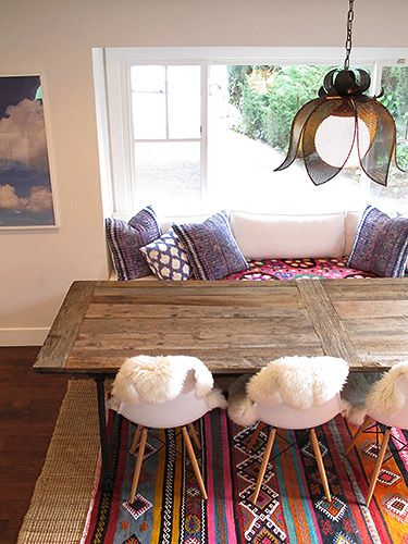 I love the old door used as a table, pops of color on rugs and pillows, Eames chairs are beautiful!!