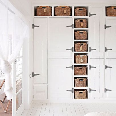 For a country version of fitted wardrobes, build a bank of cupboards of different sizes and front them with stable-style doors and oversized 'farmyard' ironmongery.