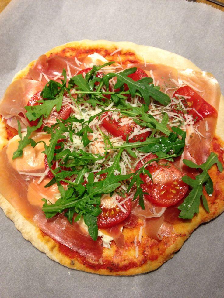 Zelfgemaakte pizza met serano ham mozzarella parmezaanse kaas tomaten en rucola en basilicum