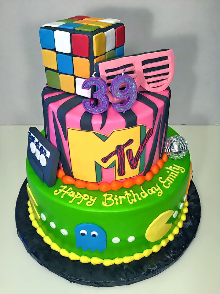 This is a 39th birthday cake with an 80's theme. It has 2 tiers with all the classic 80's memorabilia in fondant including a rubiks cube, Pac-man, MTV logo, cassette tape and 80's shades. A cool throwback cake to the 80's if you are old enough to remember!<br />