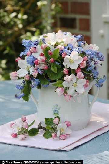 Bouquet of pink apple blossoms and forget-me-nots in nostalgic sugar bowl.