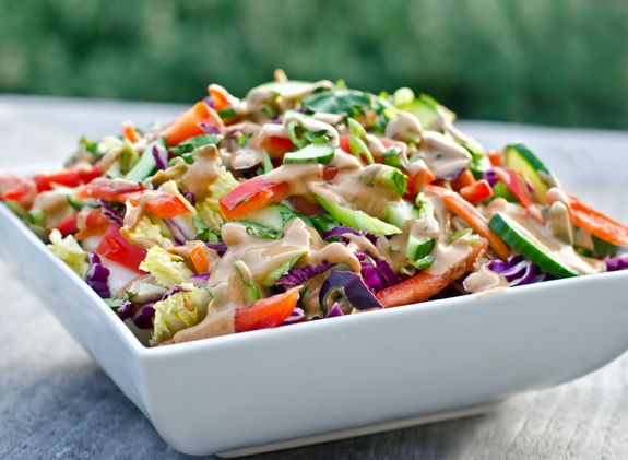 This recipe was inspired by the popular Thai Crunch Salad served at California Pizza Kitchen. It's made with crisp Napa cabbage, crunchy vegetables and edamame but it's the creamy peanut dressing -- flavored with ginger, garlic, lime and honey -- that makes it so good. I guarantee you'll want to put it on everything! You can serve this salad as a l