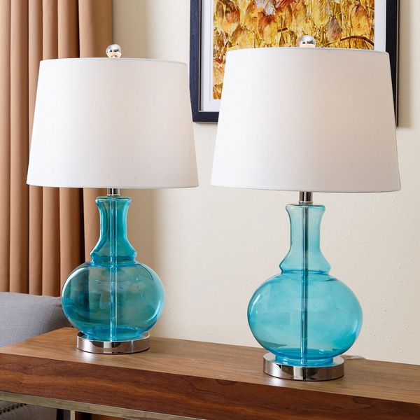 Brighten up your home with some extra lighting and a pop of color with these Abbyson Living Ellis table lamps. These lamps have a turquoise blue glass base and ivory shade with silver hardware to give