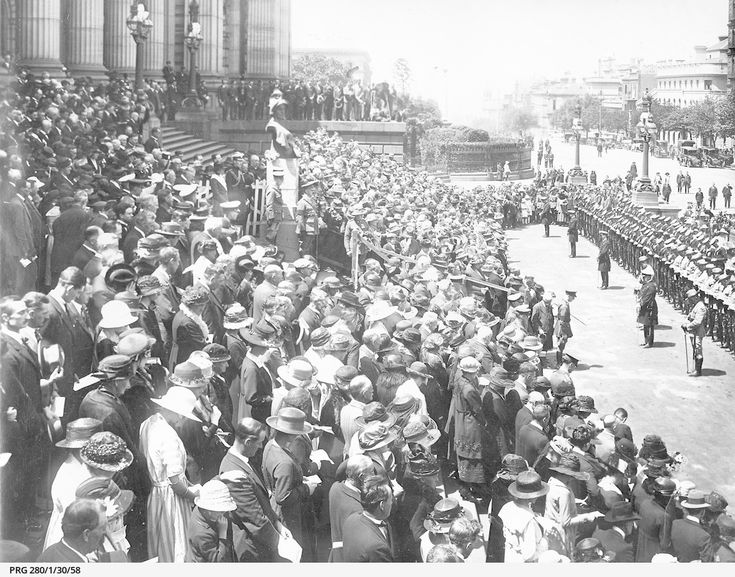 The scene outside Parliament House in Melbourne, Victoria during an Armistice Day two minute silence showing servicemen and spectators standing with bowed heads.