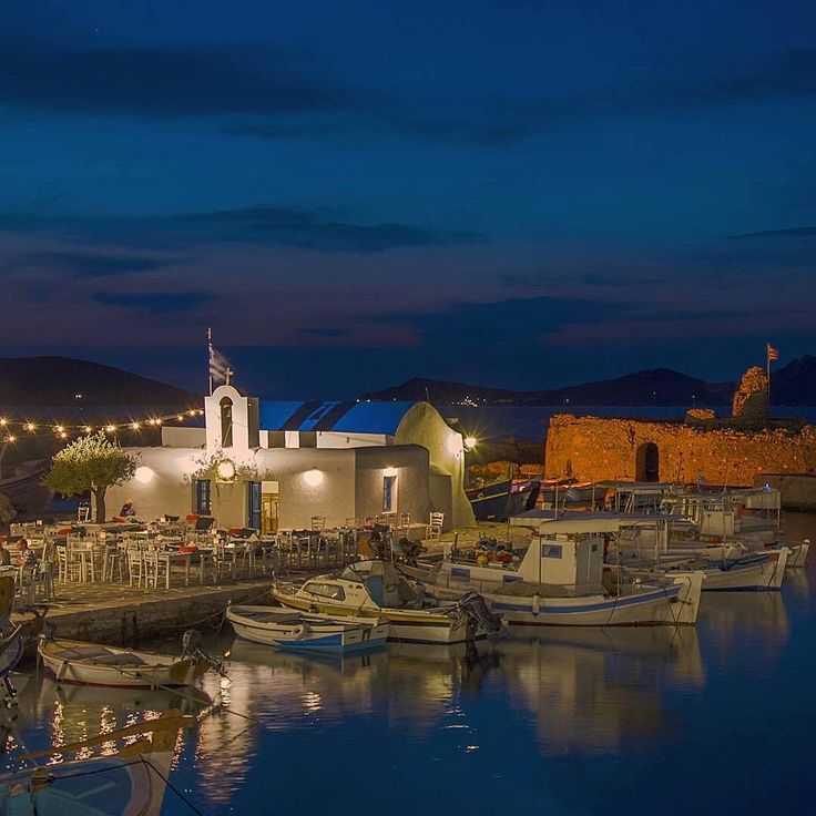 Magical Naoussa village by night , at Paros island (Πάρος). Picturesque Cycladic Church and wonderful boats in a row !