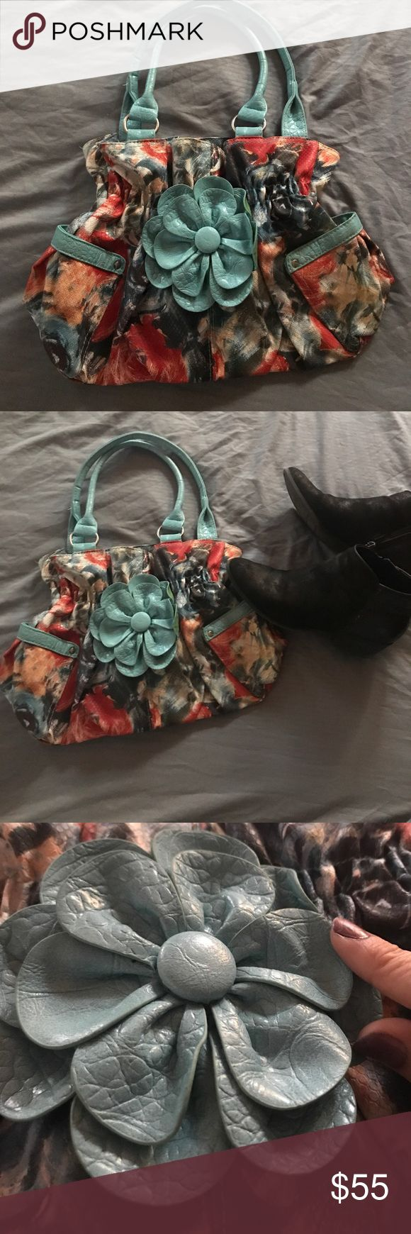 NWOT floral shoulder bag with blue leather flower NWOT cute floral shoulder bag with button closure. The bag has two side pockets on the exterior and a zipper storage pouch inside. The handles are light blue as well as the leather flower on the front. Super cute fashion piece to add to your wardrobe! Thank you for checking out my closet! Happy Shopping !! Bags