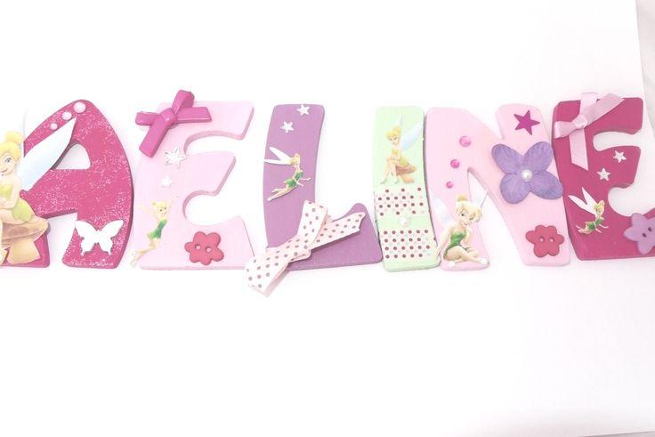 A: fushia + paillettes, fée clochette, papillon effet miroir et strass. E: rose clair, clochettes, un bouton, étoiles scintillantes et nœud. L: violet clair, clochettes, étoiles et ruban violet forme  I: vert pale, déco clochette avec du masking tape a pois rose et une perle nacré. N: rose claire, fée clochette, strass de taille différente fushia, fleure avec un cœur en perle nacré, un bouton et une étoile  E: rose fushia, clochette, étoiles scintillantes nœud rose et un bouton.