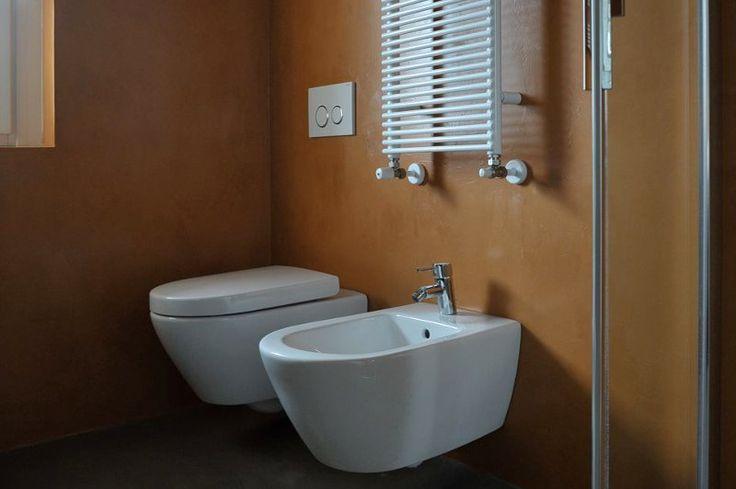 Arancione e grigio con i mobili wengè rendono l'ambiente accogliente.