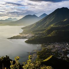 When Was Getting up for Sunrise Ever Not Rewarded? // To see the sun ascent behind Lago Atitlan in Guatemala one has to get up when the night is at its darkest; the reward is what you see here. Little towns lie in the valley by the lake before the backdrop of several, partly active, volcanoes and a tablecloth of mist still blankets the now awakening settlements. The sun has risen above the mountain ridges and plays with the slopes, deluging some with rays and shoving others into the shades.
