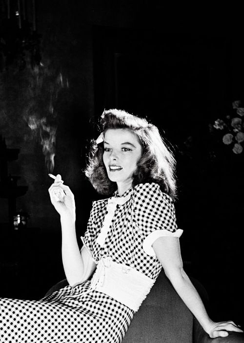 Katharine Hepburn seated on edge of chair smoking cigarette in scene from Broadway show The Philadelphia Story, 1939. Photo by Alfred Eisenstaedt.