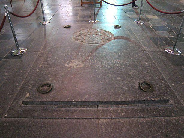 """Eingang zur Königsgruft in der Nieuwe Kerk zu Delft. Seit der Beisetzung von Wilhelm von Oranien werden Mitglieder des niederländischen Königshauses hier begraben. Die Inschrift lautet: """"RESURRECTIONEM / EXSPECTAT / GUILELMUS PRIMUS / PATER PATRIAE"""" (Wilhelm der Erste, Vater des Vaterlandes, wartet auf die Wiederauferstehung). Dieser Stein wiegt zwei Tonnen und wird allein anlässlich eines Begräbnisses geöffnet, zuletzt bei der Beisetzung von Prinz Bernhard am 11. 12. 2004…"""