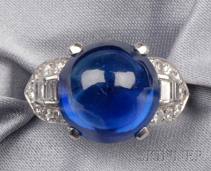 Art Deco Kashmir Sapphire and Diamond Ring, Trabert & Hoeffer Mauboussin, set with a sugarloaf cabochon sapphire measuring approx. 12.30 x 12.25 x 7.85 mm, flanked by diamond melee and baguettes, size 5 1/2, signed T & HM.