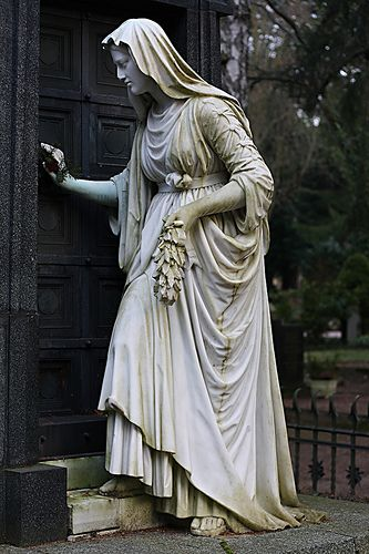 Beautiful statue of a woman opening the door to the crypt.