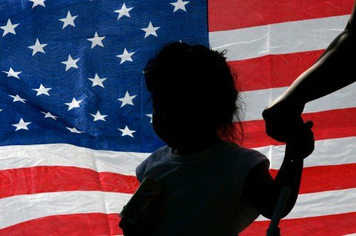A child is silhouetted against a U.S. flag at a rally in support of immigration rights in Irving, Texas October 13, 2007.  Opposing sides came out to express their views about a controversial program used by the Irving Police Department which hands undocumented workers over to federal officials for deportation proceedings. REUTERS/Jessica Rinaldi (UNITED STATES) - RTR1UW8S