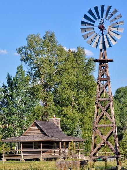 A functional windmill helps to make pastures and the surrounding grass green.  The windmill adds to the country lifestyle -- material:antique barnwood and weathered timbers