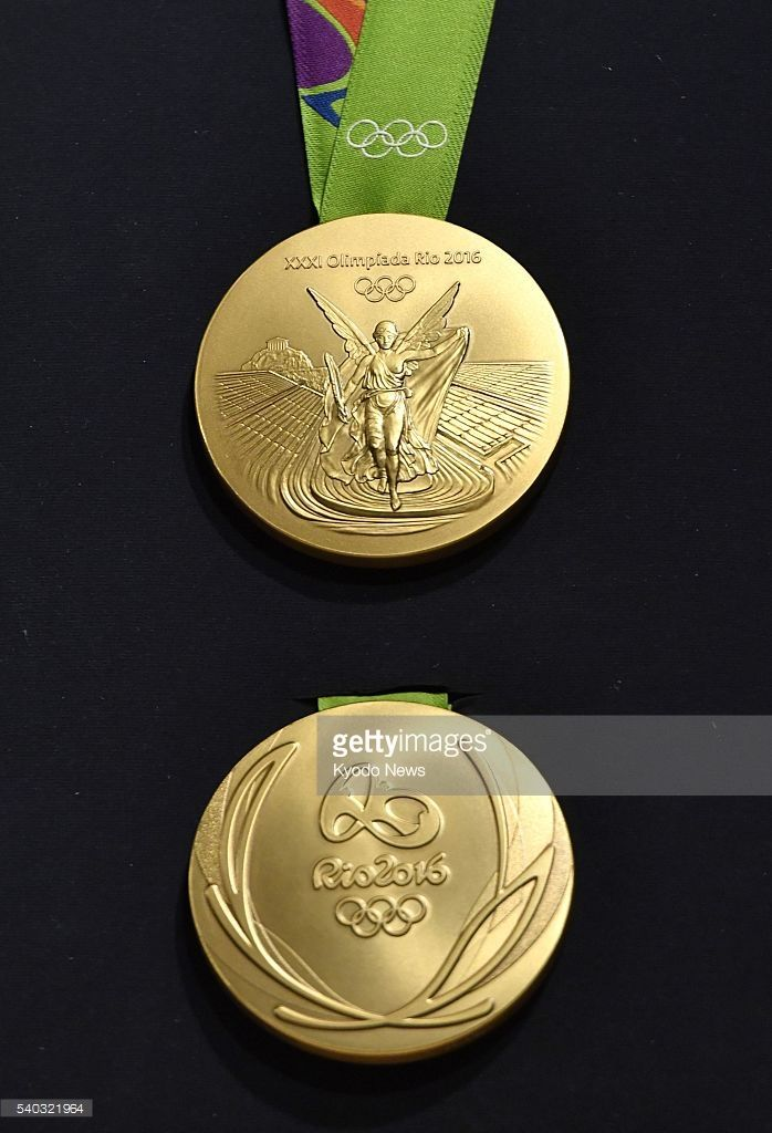 #RIO2016 Photo taken June 14, 2016, in Rio De Janeiro shows two sides of a gold medal for the 2016 Rio Olympics unveiled by the organizing committee for the event starting in August. One side (upper) represents Athens' Panathinaiko Stadium with a goddess of victory, while the other shows a design of the Olympic logo with a leaf of laurel.