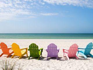 Gekleurde strandstoelen bij zee