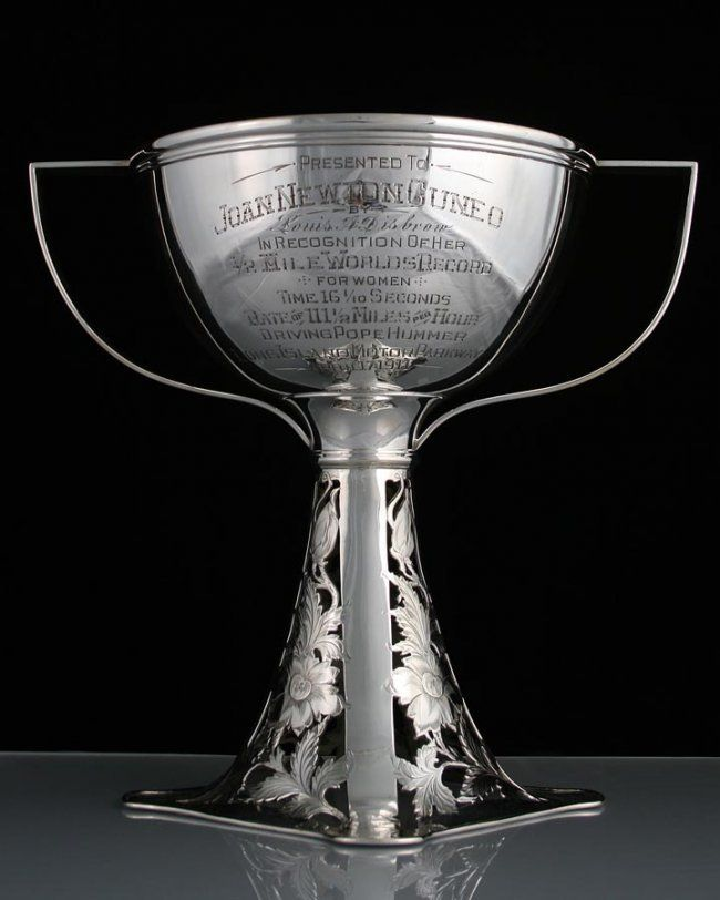 Lot 212- Joan Newton Cuneo 1/2 Mile Worlds Record Silver Plate Loving Cup Trophy. Inscribed ''Presented To Joan Newton Cuneo In Recognition of Her 1/2 Mile Worlds Record For Women, Time 16 1/10 Seconds, Rate of 111 1/2 Miles per Hour Driving Pope Hummer Long Island Parkway April 17, 1911''. 13'' x 13'', manufactured by The Van Bergh Silver Plate Co., Rochester, N.Y. NM-MT/MT
