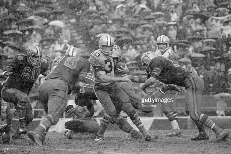 Dallas Cowboy's player Dan Reeves tries to hold on to the ball and run as a downpour turns the field to mud. The New Orleans Saints eventually beat the Cowboys in the 1967 game.