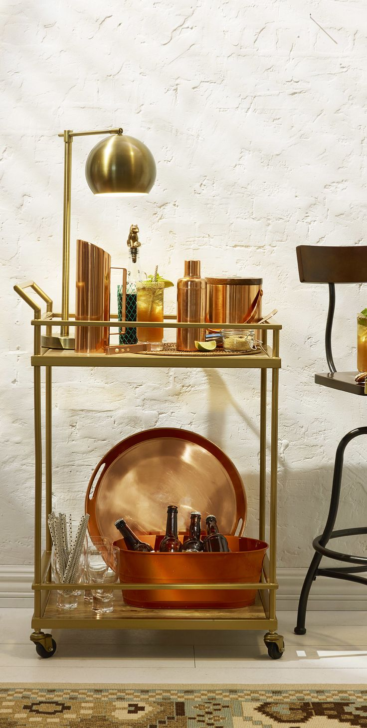 Classic tools of the drink-making trade make for a handsome two-tiered bar cart worth keeping on display.: