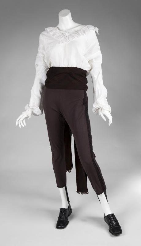 A costume worn by Jennifer Ellison in the film The Phantom of the Opera (Warner Bros., 2004) in her role as Meg Giry. The costume consists of a white linen top with ruffles and a pair of brown stirrup pants with decorative band down the side of each leg. With a brown shawl and Russell & Bromley oxford shoes.