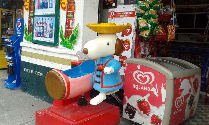"""Este Snoopy en particular es la de la serie de trajes típicos del mundo, es una máquina de montar para niños pequeños, es de los años ochentas, esta en buen estado y aun trabaja si se le inserta una moneda, también la foto muestra la tradicional """" tiendita de la esquina"""" de la Ciudad de México."""