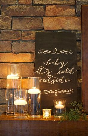 Floating candles in cylinder vase illuminating chalkboard sign.