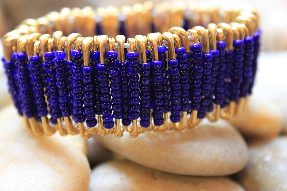 This classy and elegant royal blue and gold safety pin bracelet is a unique piece of fashionable jewelry. This bracelet is made out of glass seed beads and 7/8 gold tone safety pins. It is not only richly radiant but a piece of art that inspires conversation.  Also see: https://www.etsy.com/listing/170987564/royal-blue-and-gold-safety-pin-earrings   https://www.etsy.com/listing/171026723/royal-blue-and-gold-safety-pin-necklace