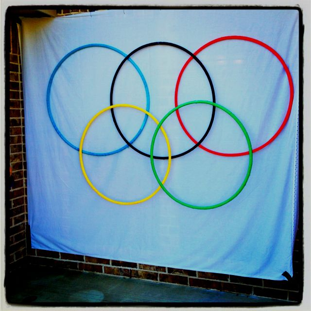 "Olympic rings for ""Olympic Birthday Party"". Hula hoops are wrapped in Olympic colored streamers and hung with fishing wire and fish hooks on a dowel rod. We used it as a back drop for a photo booth."