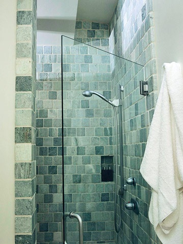 The shower is tucked behind the sink wall for privacy. Tumbled marble in the same blue-green shade as the subway tiles lines the stall. A skylight opens the marble enclosure to natural light.