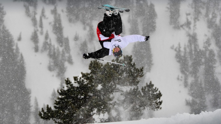 Powder White Staff doing a backflip while skiing in