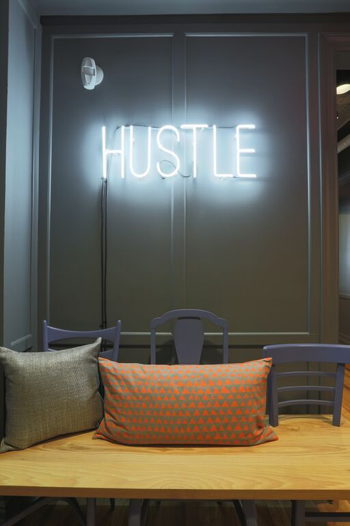 Bright lights on the walls of wework bryant park reminding members to hustle