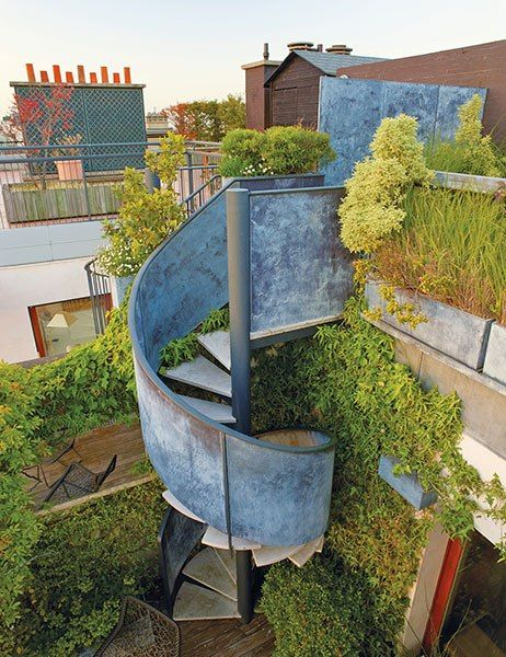 An industrial-chic staircase descends to a lush garden on the rooftop of a Paris apartment