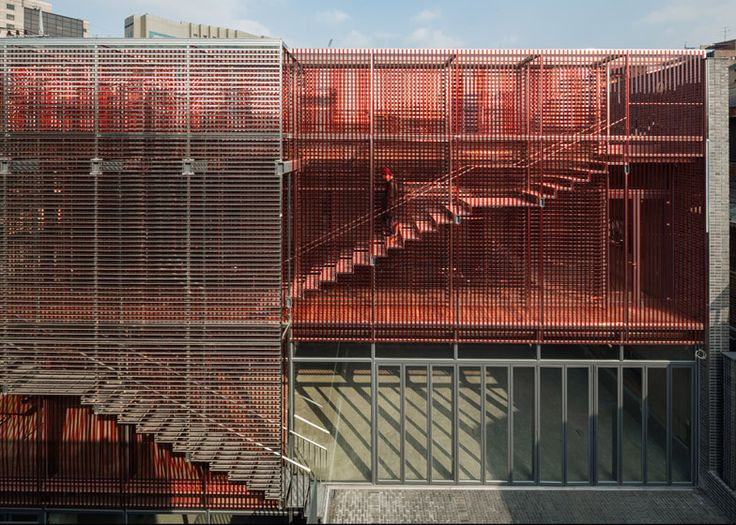 A cage-like structure made from strips of mirrored metal and red plastic encases this Seoul office building.