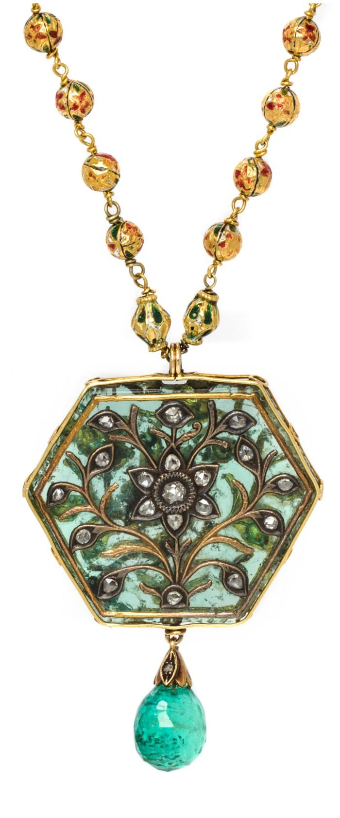 Detail; a double-strand Indian necklace with gold beads, emeralds, rubies, and an incredible natural hexagonal emerald with ruby, diamond, and gold details.