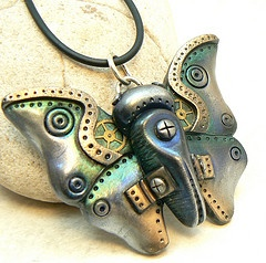 Desert Rubble, Steampunk Butterfly Pendant    Made from polymer clay and embellished with a watch gears, mica powders, and metallic wax, by Lynn Reno