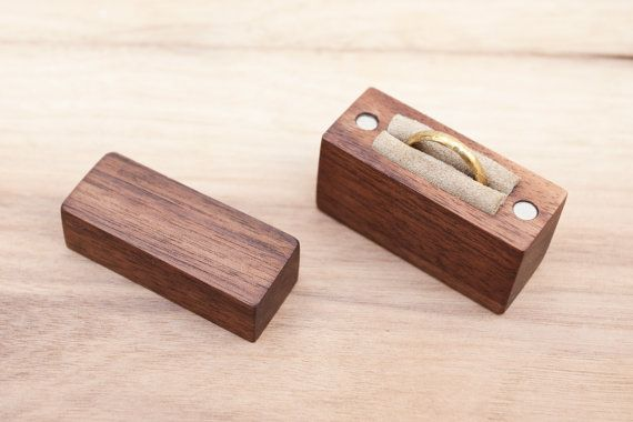 A wooden ring box, designed to hold one ring, made from black walnut wood. The two parts of the box are held together with four strong, neodymium magnets.  Made mostly with hand tools, hand sanded smooth and finished with natural walnut oil and pure beeswax. The ring is held with a piece of soft genuine leather, as shown in pictures.  Outer dimensions: 5 x 3.8 x 2 cm or 1 31/32 x 1 1/2 x 13/16 Inner dimensions: 3 x 2.8 x 1.2 cm or 1 3/16  x 1 7/64 x 15/32  Please make sure your ring will…