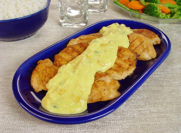 Na foto, o frango grelhado com creme de milho está em uma travessa oval, de vidro azul. Na foto aparecem 4 filés bem dourados e combertos com o creme de milho. Na decoração ao fundo está uma tigela de arroz e outra com salada de legumes.