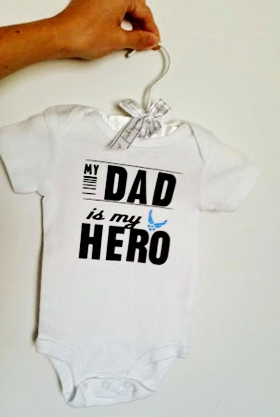 """A baby one piece to show how much baby loves daddy (or mommy!). Original design with Air Force wings says """"My Dad is my Hero"""" Customizeable to say Mom instead of Dad. Celebrate the military heroes in"""