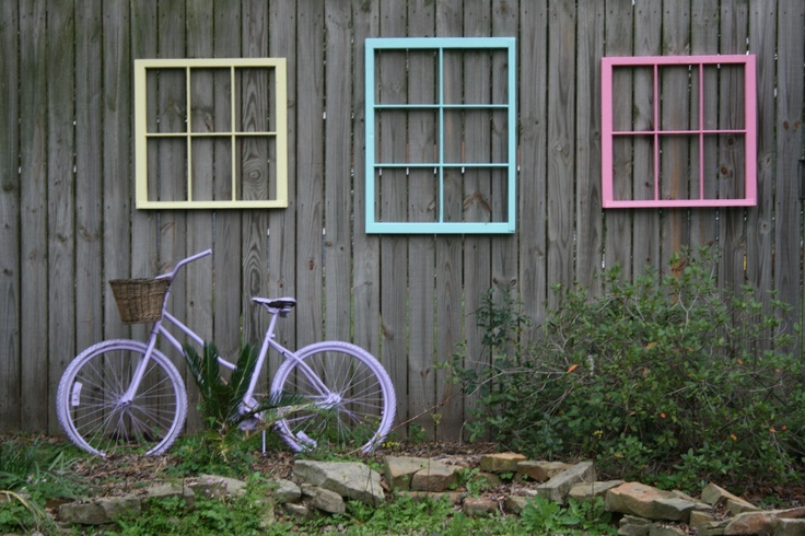 As part of a junk habit, I took old windows, painted them and then painted an old bike to use as yard art in a place where my plants will not grow.