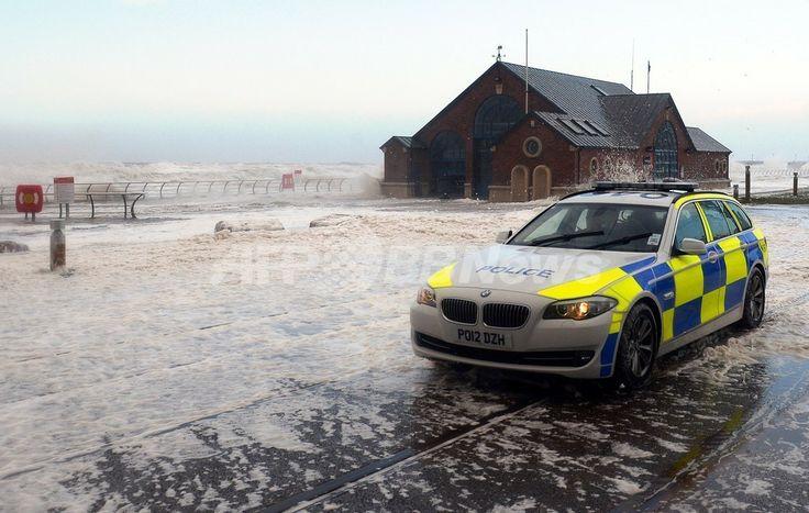 英イングランド(England)北西部ブラックプール(Blackpool)で、高潮で冠水した沿岸沿いをパトロールするパトカー(2013年12月5日撮影)。(c)AFP/PAUL ELLIS ▼6Dec2013AFP|欧州に60年ぶりの猛烈な嵐、満潮と重なり警戒態勢強化 http://www.afpbb.com/articles/-/3004568