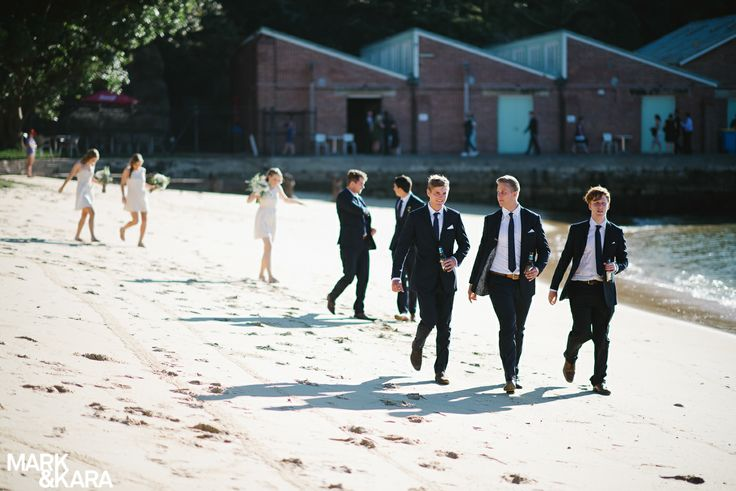 Bride and groom with bridal party on the beach, Sydney wedding. On location at Q Station, Manly. The groomsman looking smooth in their matching suits.